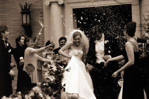 Dallas, Texas, USA --- Wedding Party Throwing Rice at Newlyweds --- Image by © Jack Hollingsworth/Corbis